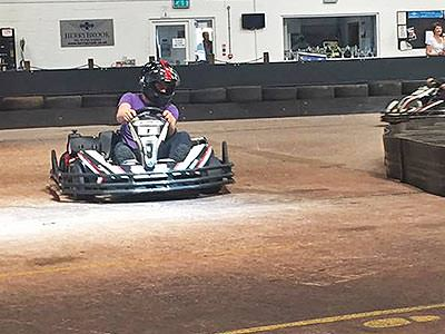 A man driving a go kart around a corner at a quick pace, on an indoor track