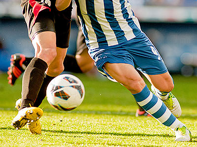 The legs of two footballers going in for a tackle