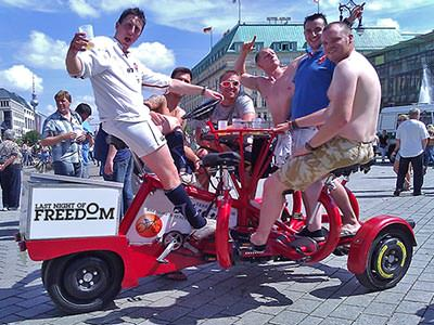 Men sitting on a red 'conference'-style beer bike