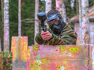 A man aiming with a paintball gun in camouflage gear and a mask, whilst standing behind a half fence