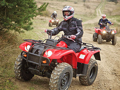 A man driving a red quad bike in the country, with two people driving in the background