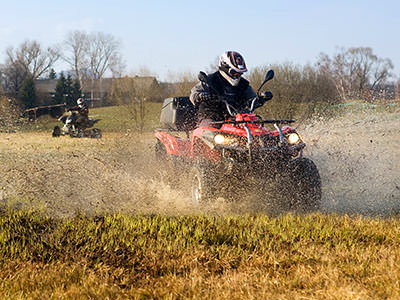 A man driving a red quad bike through a muddy field, with two people driving in the background