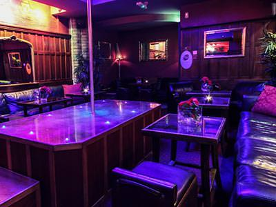 An empty strip club with seating, tables and a podium with a pole