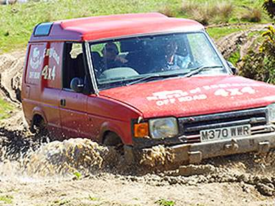 A red 4x4 driving through the mud