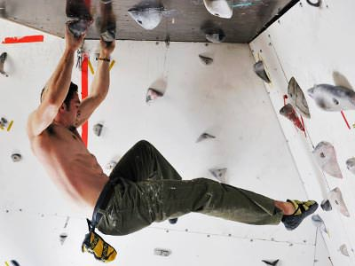 A topless man on a bouldering wall