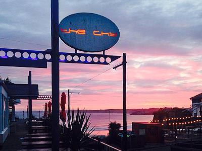 The Chy Bar exterior sign at sunset, with the coast in the background