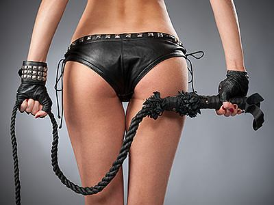 A woman wearing just her knickers, with a whip held behind her back