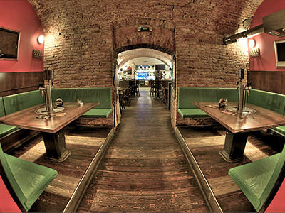 Green booths along a wall with beer taps in the middle of tables