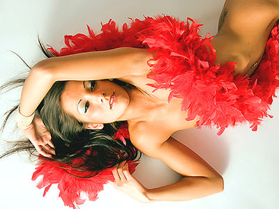 A naked woman lying on her back with a red feather boa on top of her