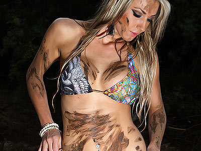 A woman in a bikini top with mud marks on her stomach, arm and face