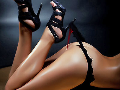 A woman holding her thong up with her stiletto heel