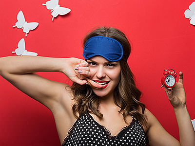 A woman wearing a blue eye mask on her head and holding an alarm clock to a red backdrop