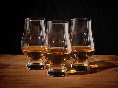 Three whiskey glasses with whiskey in