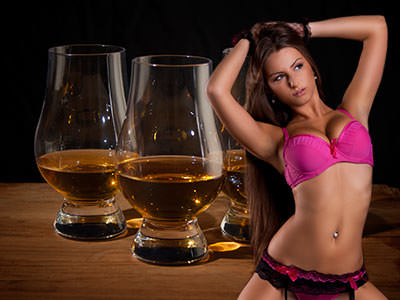 A woman posing in pink underwear in front of an image of whiskey in glasses