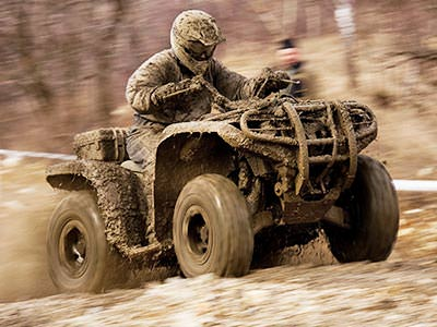 A person in overalls and mud, driving a muddy quad bike