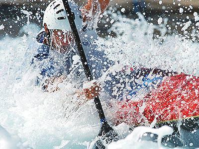A person paddling a kayak through foamy rapids