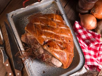 A large piece of cooked meat in a tray, with onions, a napkin and cutlery around it