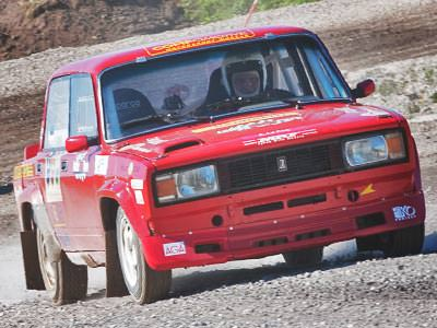 A red Lada car driving on a gravel road