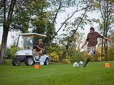 A man kicking a football on a golf course, whilst a man looks on in a golf buggy in the background