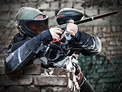 A man wearing a paintball mask leaning on a brick wall and aiming a paintball gun