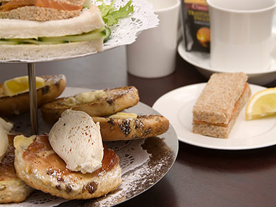 Scones with clotted cream and sandwiches on a cake stand, with tea and a sandwich on a white plate in the background