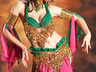 A woman poses in a traditional belly dancing outfit