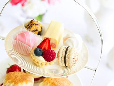 A close up of the top layer of an afternoon tea, with delicate sweet bites