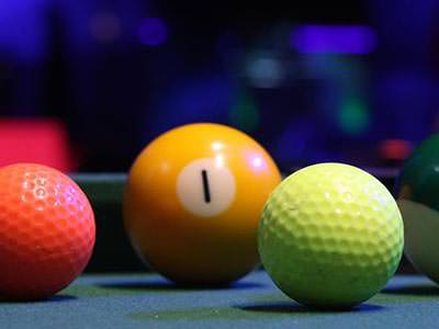A yellow snooker ball next to two golf balls on a table