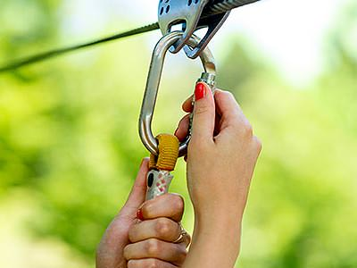 A pair of hands attaching a carabiner to a metal cable