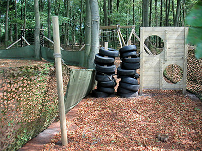 An assault course with tyres and wooden boards with holes in