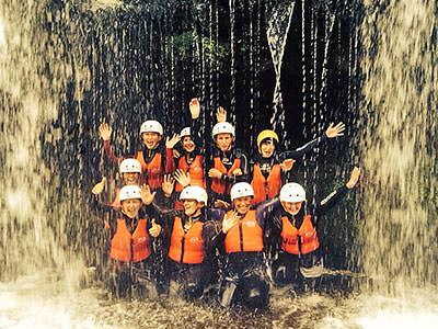 Nine people standing under a waterfall wearing with lifejackets on and helmets