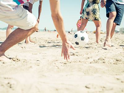 Close up of men's legs, playing football on the beach