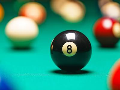 The black snooker ball in focus in the foreground on a snooker table