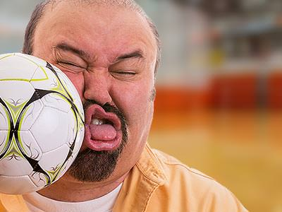A man being hit in the face with a football