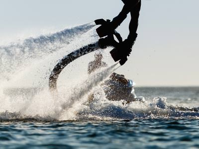 A pair of legs operating a flyboard, just above the surface of some water