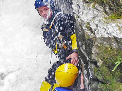 A man gorge scrambling and being splashed with water in a wetsuit and a helmet