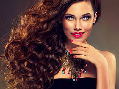 Close up of a woman in black and a jewelled necklace, posing with long brown hair loose