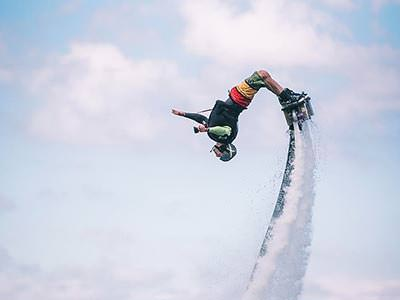 A man flips over headfirst on a flyboard