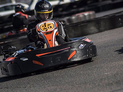 A man racing on an outdoor karting track, with another man in the background