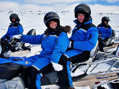 A man and women wearing blue snowsuits and helments posing on a snowmobile, with other people and snowmobiles in the background