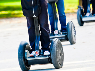 Close up of people riding Segways outdoors