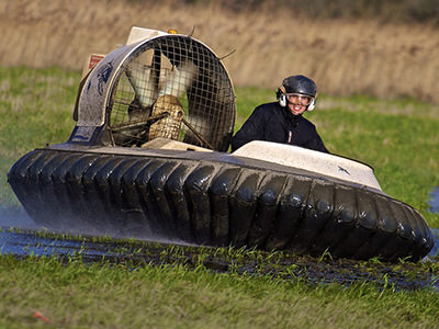 A hovercraft being driven over a wet field