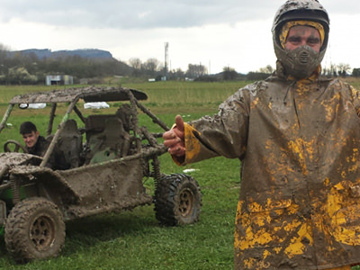 A man in a muddy jacket in front of a dirt buggy with someone sitting in it