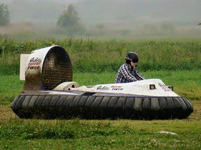 A person in a checked shirt driving a hovercraft in a field