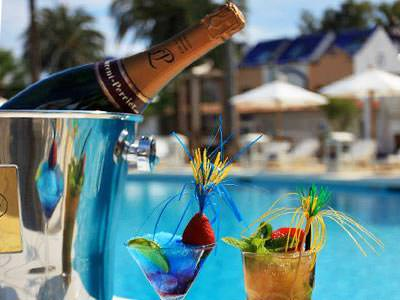 Champagne bottle in a silver ice bucket alongside two glasses of cocktail, with a blurry pool and sun loungers in the background