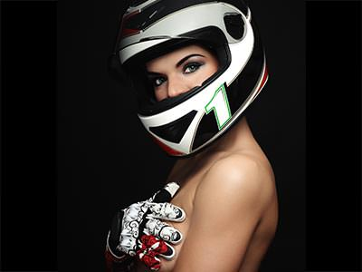 A topless woman wearing a racing helmet and with a gloved hand over her chest