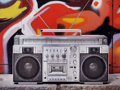 A boombox-style radio cassette player in front of a red, graffiti'd wall