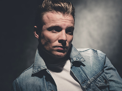 A man wearing a denim jacket and with slicked back hair