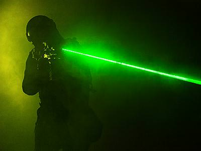 A silhouette of a man aiming a rifle that's emitting a visible green laser