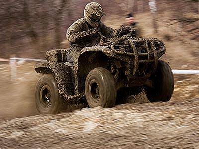 A mud-covered man driving a mud-covered quad bike